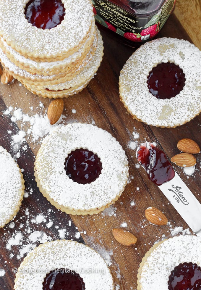 A recipe for the Traditional Raspberry Linzer Cookies | A delightful rolled almond cookie filled with raspberry preserves and dusted with powdered sugar! A new Christmas favorite!
